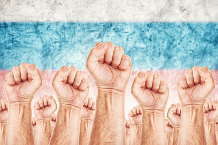 Russia Labour movement, workers union strike concept with male fists raised in the air fighting for their rights, Russian national flag in out of focus background.