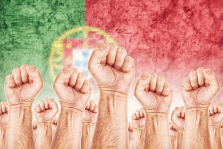 Portugal Labour movement, workers union strike concept with male fists raised in the air fighting for their rights, Portuguese national flag in out of focus background.