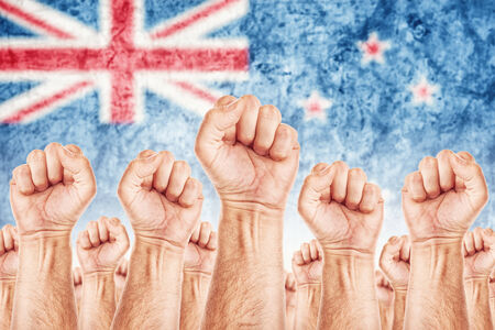 New Zealand Labour movement, workers union strike concept with male fists raised in the air fighting for their rights,  New Zealand national flag in out of focus background.