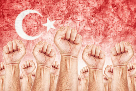 Turkey Labour movement, workers union strike concept with male fists raised in the air fighting for their rights, Turkish national flag in out of focus background.