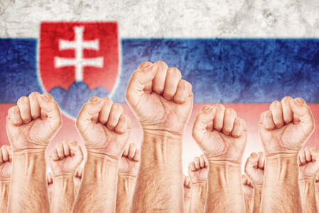 Slovakia Labour movement, workers union strike concept with male fists raised in the air fighting for their rights, Slovak national flag in out of focus background.