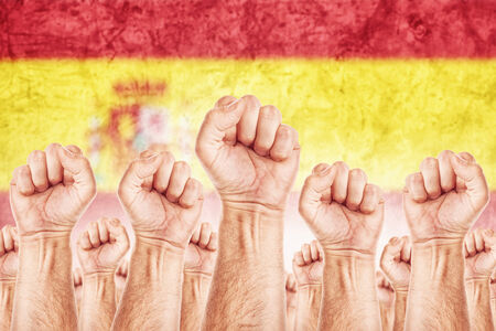 Spain Labour movement, workers union strike concept with male fists raised in the air fighting for their rights, Spanish national flag in out of focus background.
