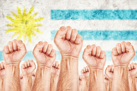 Uruguay Labour movement, workers union strike concept with male fists raised in the air fighting for their rights, Uruguayan national flag in out of focus background.