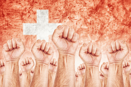 Switzerland Labour movement, workers union strike concept with male fists raised in the air fighting for their rights, Swiss national flag in out of focus background.