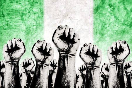 Nigeria Labor movement graphic concept, workers union strike concept with male fists raised in the air fighting for their rights and Nigerian national flag in out of focus background.