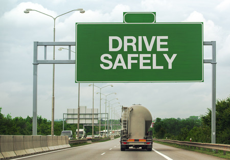 Fuel Tanker Truck on Highway Road Passing by Drive Safely Sign as a Reminder for Safety in Traffic and Accident Prevention Concept.