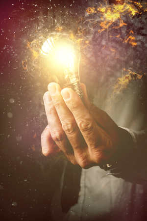 Energy of new ideas in business process, businessman with light bulb as metaphor of new ideas, innovation and creativity, retro toned image, selective focus.