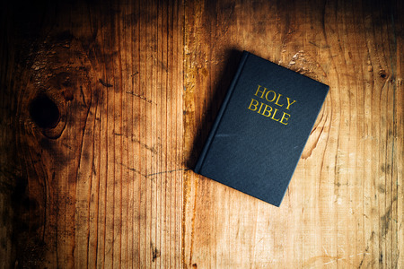 Holy Bible on old wooden church table, top view