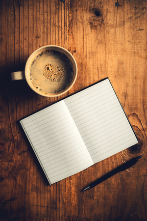 Top view of open notebook with blank pages, writing pencil and cup of coffee on old wooden desk, retro toned image