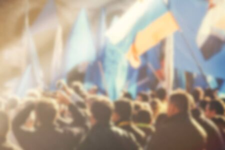 Blur unrecognizable crowd at political meeting, cheering audience looking at the stage and supporting political party, defocussed retro toned image with lens flare.