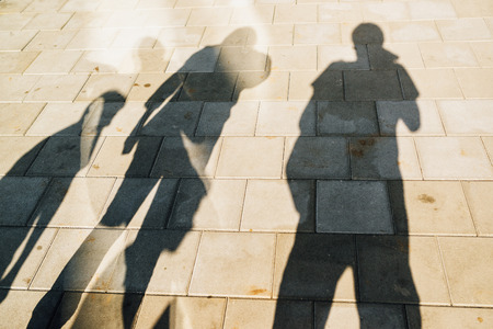 People casting shadows on the pavement, four young man and women overshadowing street concrete tiles