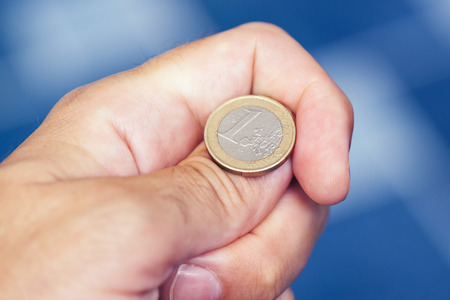 Businessman hand tossing coin to flip on heads or tails, concept of chance, opportunity and decision making