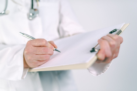 Female doctor in white uniform writing on clipboard paper patient's medical history or medicine prescription. Woman as health specialist in exam, er, disease prevention, visit check or healthcare lifestyle concept