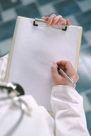 Female doctor in white uniform writing on clipboard paper as copy space for patient's medical history or medicine prescription. Woman as health specialist in exam, er, disease prevention, visit check or healthcare lifestyle concept
