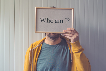 Who am I, self-knowledge concept with question covering adult male face