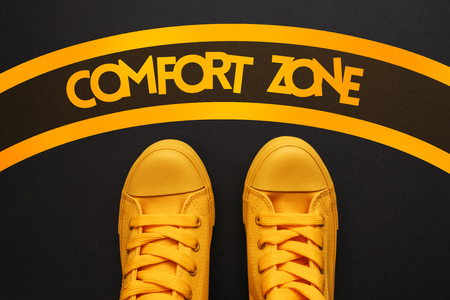 Photo pour Comfort zone concept, young adult person in yellow sneakers standing inside of the circle, top view - image libre de droit