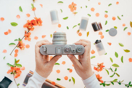 Photo for Woman holding vintage camera over springtime floral decoration, spring season is great for starting a new hobby like photography - Royalty Free Image