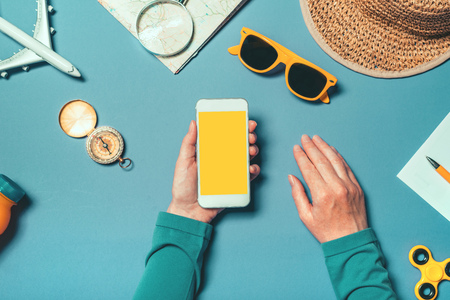Foto de Smartphone mock up in summertime holiday vacation concept, woman holding mobile phone with blank screen as copy space, top view overhead shot with flat lay arranged summer accessories - Imagen libre de derechos