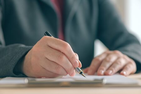 Photo pour Businesswoman signing contract and business partnership agreement at office desk, close up of hands writing signature - image libre de droit