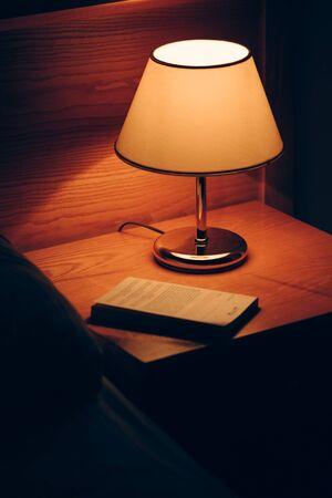 Foto de Book and vintage lamp on night table in hotel room. Retro styled bedroom interior. - Imagen libre de derechos