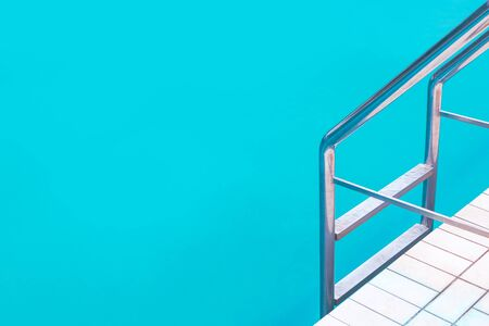 Outdoor swimming pool water and aluminum ladder with no people, summer vacation holiday abstract background