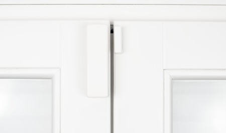 Photo pour Wireless battery magnetic alarm sensor for window and door on white wooden sash detail - image libre de droit