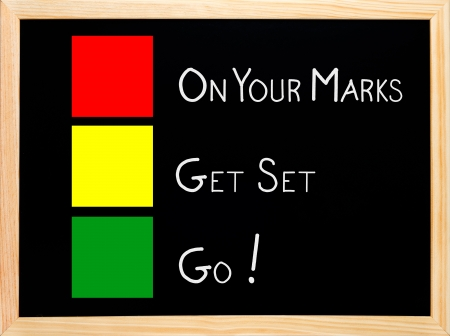 On Your Mark, Get Set, Go written on blackboard or chalkboard with traffic light red yellow green colors
