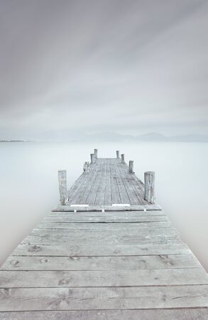 Wooden pier in a cloudy and foggy mood  A long exposure photography taken in autumn