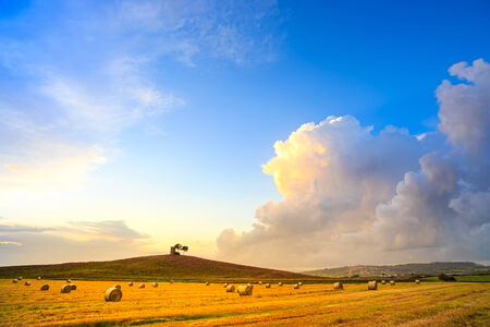 Tuscany, Maremma typical countryside sunset landscape and thunderstorm cloud Hill, trees, straw bales and rural tower