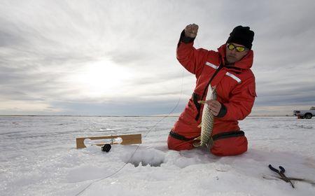 Photo pour A man with a northern pike on a frozen lake - image libre de droit