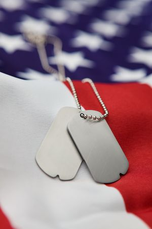 Vertical blank dog tags on American flag with focus on tags - Shallow dof