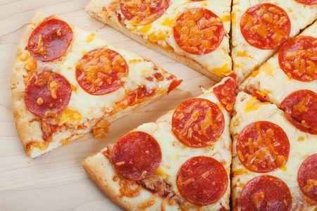 Pepperoni pizza closeup on wood ready to serve