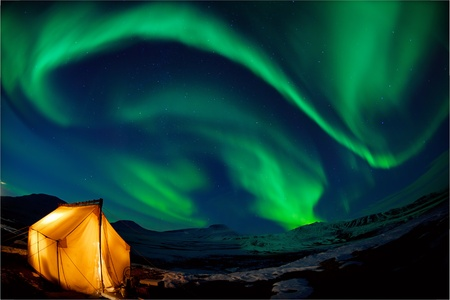 Camping in the north with the northern lights overhead (Aurora Borealis)