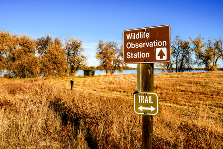 A sign points to a wildlife observation station, the wood hut in the background, at Barr Lake State Park northeast of Denver, Colorado, on a fall morning. A bird watcher contemplates the scene.