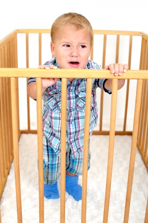 Small angry boy is crying in playpen