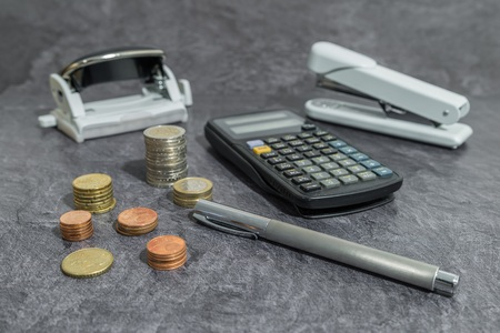 Money and office accessories on a desk
