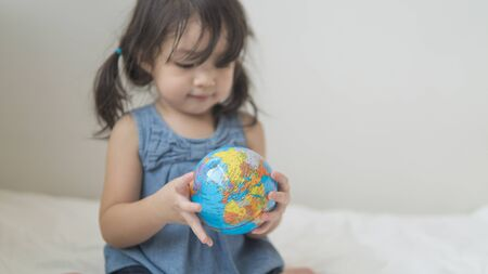 Photo for Close-up of globe ball in asian toddler hands. - Royalty Free Image