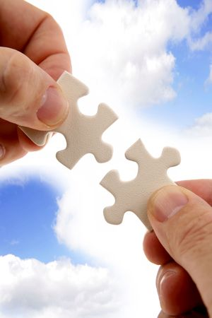Fingers holding two puzzle pieces in front of blue sky.