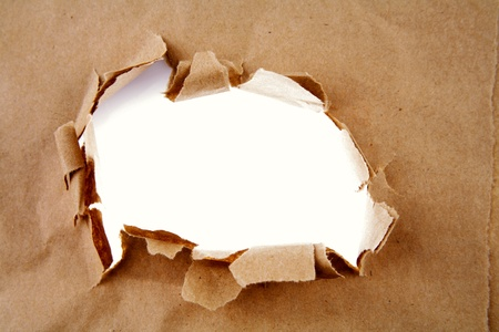 Hole ripped in brown paper