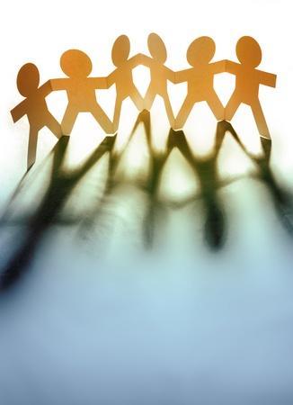 Photo pour Paper chain people holding hands - image libre de droit