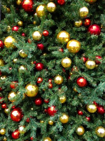 Closeup of gold and red christmas baubles on tree