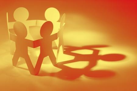 Foto de Group of paper doll people in a circle holding hands  Teamwork concept - Imagen libre de derechos