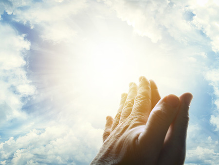 Hands together praying in bright sky