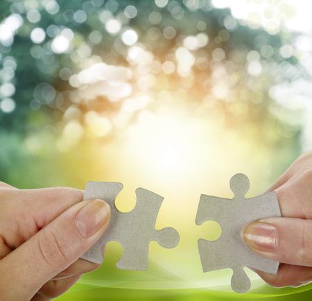 Photo pour Fingers holding two puzzle pieces - image libre de droit