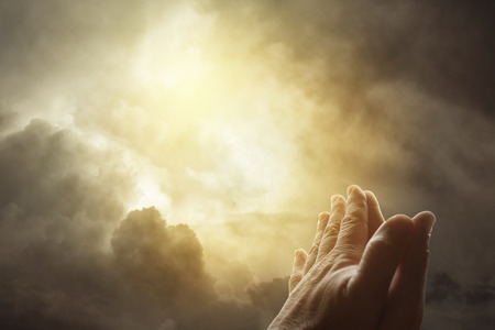 Photo for Hands together praying in bright sky - Royalty Free Image