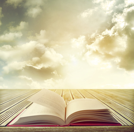 Open book on table in front of bright sky