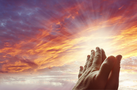 Photo pour Hands together praying in bright sky - image libre de droit