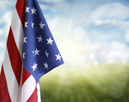 American flag in front of blue and green background