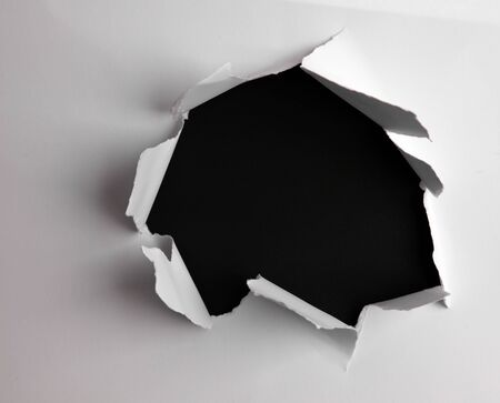 Photo for Hole ripped in paper on black - Royalty Free Image