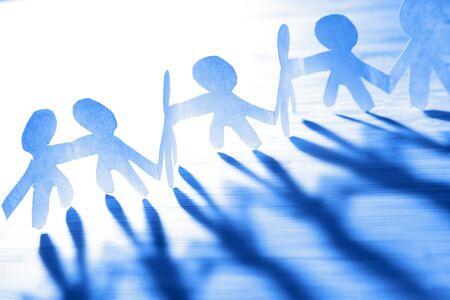 Foto de Team of paper chain people holding hands. Blue tone. Teamwork. Partnership. - Imagen libre de derechos